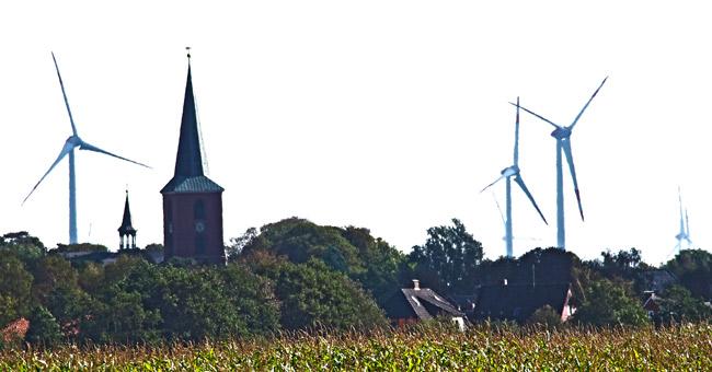 Der Kirchturm von Esens, im Hintergrund der vier Kilometer entfernte Windpark Stedesdorf, Foto (C): Manfred Knake